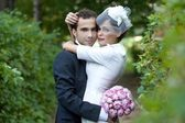 Happy bride and groom on their wedding. Bride and groom embracing in the middle of nature. — Stock Photo