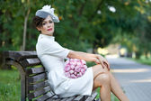 Wedding. Beautiful bride in stylish sheath dress with a hat veil sitting on a bench with a bouquet of flowers. — Stock Photo
