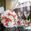 Wedding. Bridal bouquet and wine glasses on a table. — Stock Photo #51521663