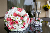 Wedding. Bridal bouquet and wine glasses on a table near the newlyweds home. — Stock Photo