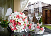 Wedding. Bridal bouquet and wine glasses on a table. — Stock Photo