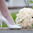 Wedding shoe and bridal bouquet. Female feet in white wedding shoes and bouquet of fresh white roses close-up. — Stock Photo