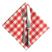 Vintage knife and fork on red plaid linen napkin isolated on white background. — Foto Stock