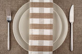 Table setting. Beige plate, fork, knife and beige linen napkin and tablecloth. — 图库照片