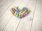 Colourful Valentine sweets or Easter eggs heart on white wooden floor — Stock Photo