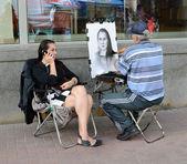 Street artist draws a girl on the Arbat — Stock Photo