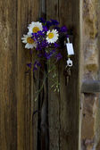 Vintage wooden door with a bouquet — Stock fotografie