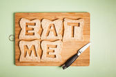 Eat me text carved out of brown bread slices — Stock Photo