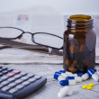 Medicine bottle, pills and financial data — Stock Photo