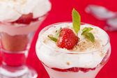 Two strawberry and cream desserts on red background — Stock Photo