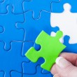 Woman's hand placing missing piece in Jigsaw puzzle signifying — Stock Photo