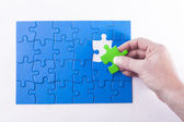 Woman's hand placing Jigsaw puzzle piece off different color sig — Stock Photo