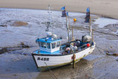 Battered fishing boat at low tide in harbour with ragged flags — Stock Photo