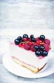 Cheesecake with raspberries, red and black currants — Stock Photo