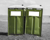 Green mobile toilet on a black and white beach — Stock fotografie