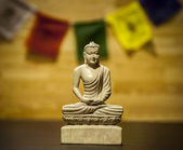 Buddha statue with prayer flag — Photo