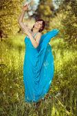 Girl in a beautiful blue fluttering dress. — Stock Photo