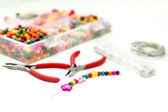 Bracelet made of plastic beads for girls unfinished in process of completing — Stock Photo
