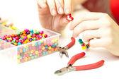 Renkli plastik boncuk kolye yapma kadın — Stok fotoğraf