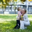 Beautiful boy and mom in spring park with present. Mothers day or birthday celebration concept — Stock Photo #46009585