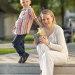 Beautiful boy and mom in spring with present. Mothers day or birthday celebration concept — Stock Photo #46009607