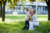 Beautiful boy and mom in spring park with present. Mothers day or birthday celebration concept — Stok fotoğraf