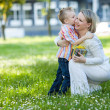 Beautiful boy and mom in spring park with present. Mothers day or birthday celebration concept — Stock Photo #46095337