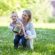 Beautiful boy and mom in spring park with present. Mothers day or birthday celebration concept — Stock Photo #46095357