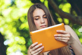 Beautiful young woman sitting on the bench in park with tablet — Stock Photo