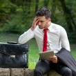 Concerned young business man sitting in city park holding computer tablet — Stock Photo #50209731