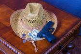 Hat, handgun and money on wooden desk — Stock Photo