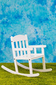 White child s chair on sky and grass backround — Stock Photo