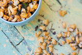 Fresh chanterelles in the bowl on a wooden board — Stock Photo