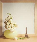 Ikebana and vintage photo-frame on table — Stock Photo