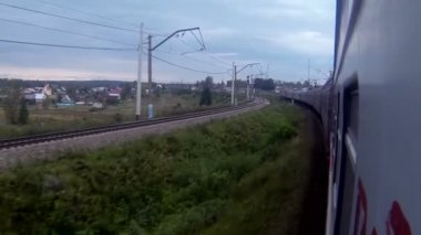 Train in a sharp curve while passing by a village — Wideo stockowe