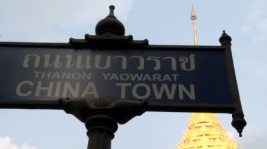 Tilt down from Chinatown sign to the street in front of the Phra Maha Mondop Wat Traimitr Witthayaram — Stock Video
