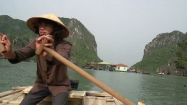 Vietnamese guy rowing the boat with tourist in it — Stock Video