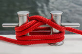 Red rope fasten on stake of yacht — Stock Photo