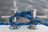 Blue rope fasten on stake of yacht — Stock Photo