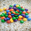 Small bright colored candies on stones — Stock Photo #50505627