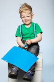 Child boy cutting colored paper with scissors — Stock Photo