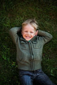 Little boy lying on grass and laughing — Stock Photo
