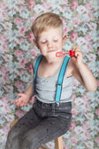 Beautiful joyful blond boy blowing soap bubbles — Stock Photo