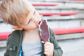 Kid eating chocolate ice-cream outdoor — Stock Photo