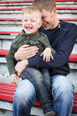 Father and son laughing in empty stadium — Stock Photo