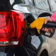 Woman filling up car at petrol station black car — Stock Photo