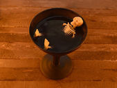 Skeleton in cup of wine — Stock Photo