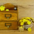 Wooden box with pocket watch, gift and yellow flowers in a cup — Stock Photo #46314511