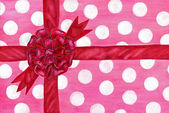 Gift in a spotted wrapping paper with bow — Stock Photo