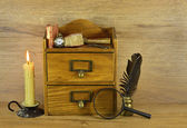Wooden box with old written implements and burning candle — Stock Photo